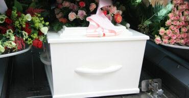 É possível ver caixão envolto em flores. Inicia-se o processo de como é feito o traslado de corpos.