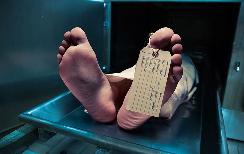 Cadáver com etiqueta no pé ilustrando as burocracias no traslado de corpos