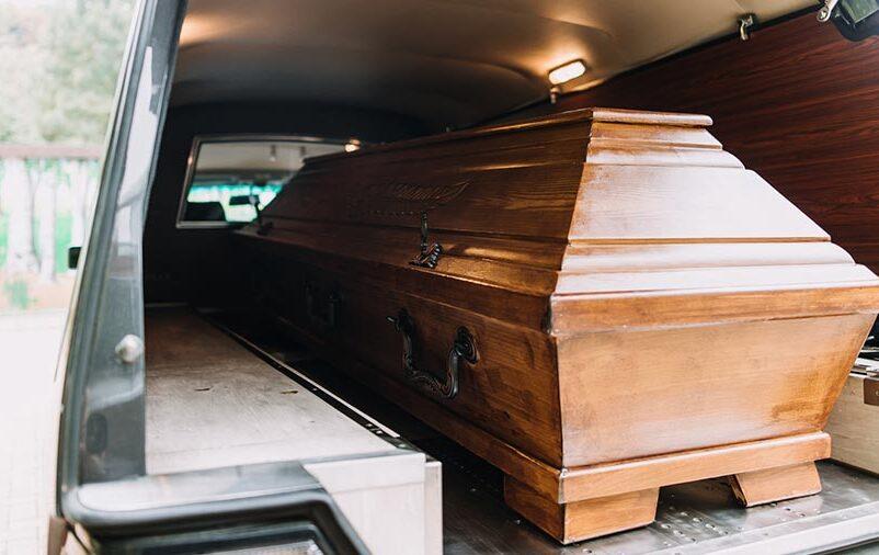 Caixão dentro do carro fúnebre representa quando solicitar o traslado de corpos