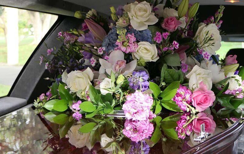 Vemos um caixão e flores dentro de um carro fúnebre. Conheça os benefícios de contratar a Central Traslado!